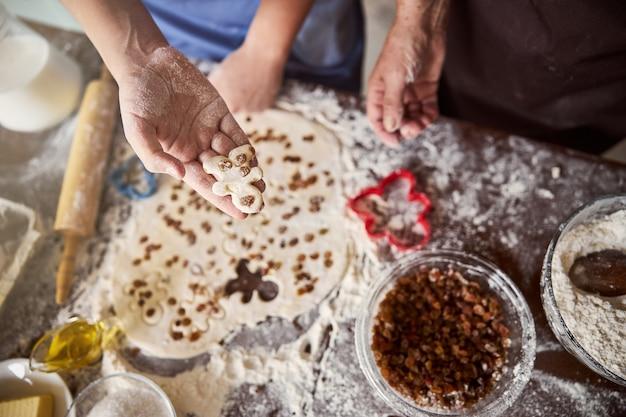 Familienaktivität zur herstellung von lebkuchenmännern mit einem schuss rosinen