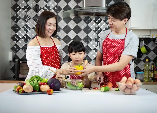 Familienasiat, der in der küche kocht
