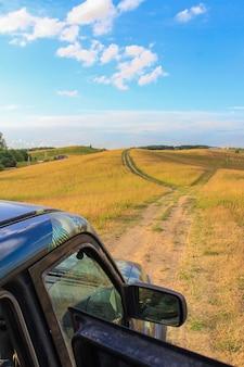 Familienausflug mit einem großen auto im gelände. halten sie auf den hügeln an, um die wunderschöne landschaft zu bewundern. sommer outdoor-aktivitäten
