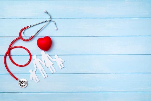 Familienausschnitt und stethoskop auf blauem holz
