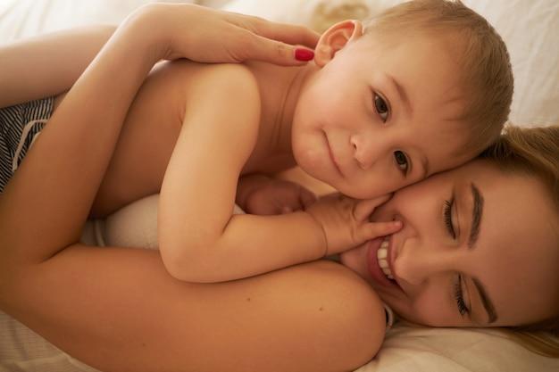 Familienbande und mutterschaftskonzept. beschnittenes bild der schönen jungen europäischen mutter, die im schlafzimmer entspannt auf weißen laken mit ihrem entzückenden kleinen sohn liegt, ihn festhält und glücklich lächelt