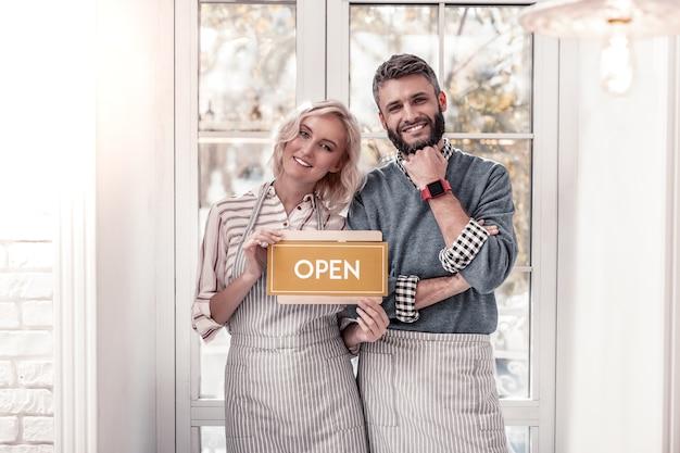 Familienbetrieb. erfreutes fröhliches paar, das zu ihnen lächelt, während es sein eigenes café eröffnet