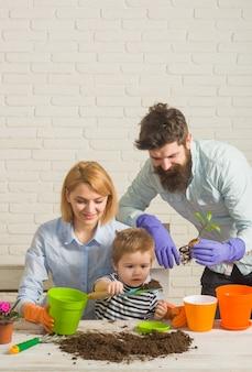 Familienbeziehungen, die familie pflanzen, die blumen pflanzt, sohn hilft der mutter, sich um pflanzen im garten zu kümmern