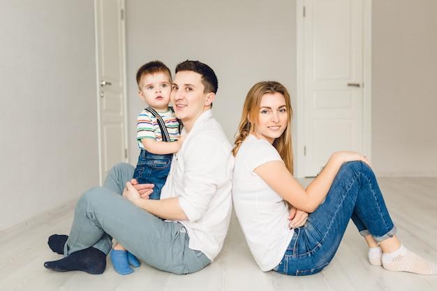 Familienbild von zwei jungen eltern, die mit ihrem jungenkind spielen
