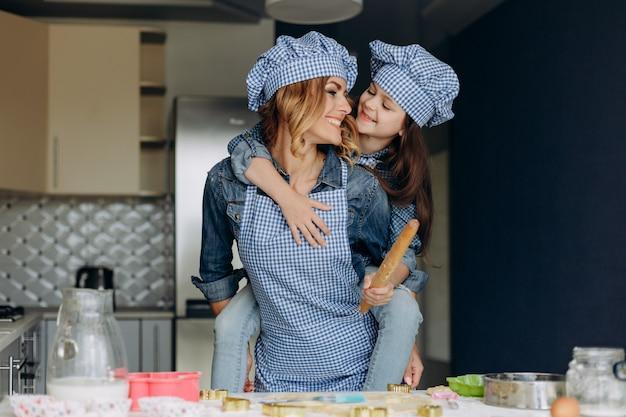 Familienblickmädchen und -mutter, die in der küche kochen.