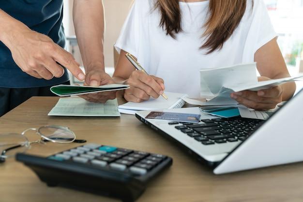 Familienbudget und finanzen. junge frau, die konten zusammen mit ihrem ehemann zu hause macht,