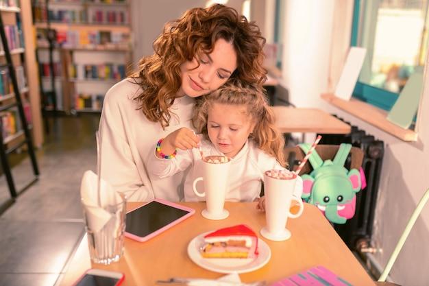 Familiencafé. ernstes mädchen, das ihr getränk betrachtet, während freizeit im café genießt