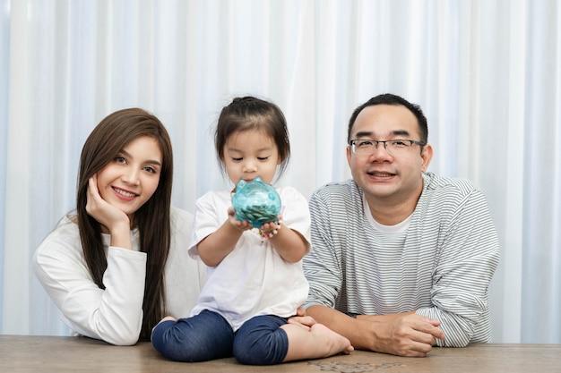 Familieneinsparungen, budgetplanung, taschengeld für kinder. asiatische familienmutter und tochter zeigen sparschwein spardose
