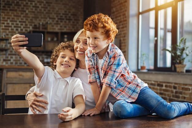 Familienerinnerungen. selektiver fokus auf eine schöne ältere frau und einen kastanienhaarigen jungen, der breit grinst, während er auf eine frontkamera eines telefons schaut und zu hause selfies macht.