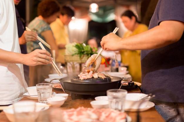 Familienessenhand mit essstäbchen, das praw auf heißer grillpfanne kocht.