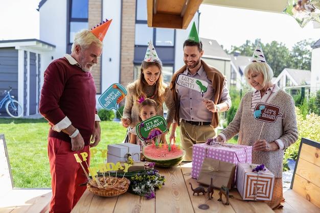 Familienfeier. erfreutes mädchen, das nahe eltern steht, während sie ihre geschenke betrachtet