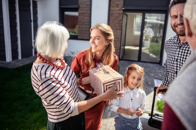 Familienfeier. glückliche reife frau, die positivität ausdrückt, während geschenkbox hält