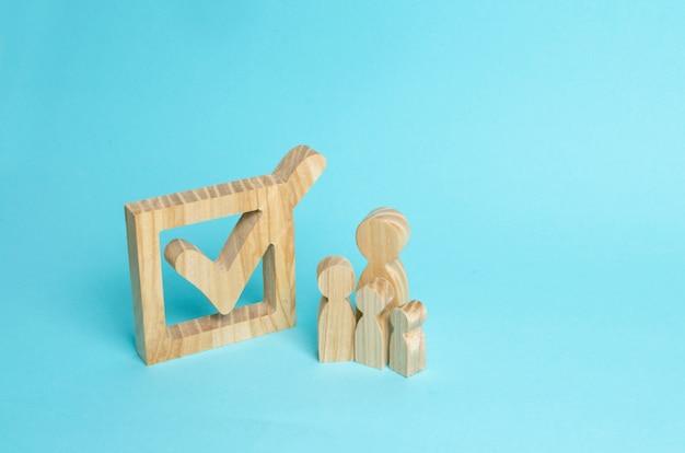 Familienfiguren aus holz stehen neben einem häkchen im kasten.