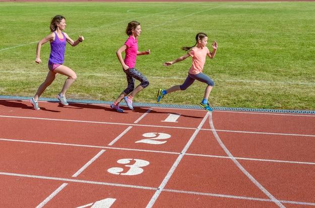 Familienfitness, mutter und kinder, die auf stadionbahn, training und kinder laufen, tragen ein gesundes lebensstilkonzept