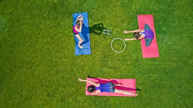 Familienfitness und sport im freien, gruppe der aktiven mädchen, die im park trainieren, luftansicht von oben