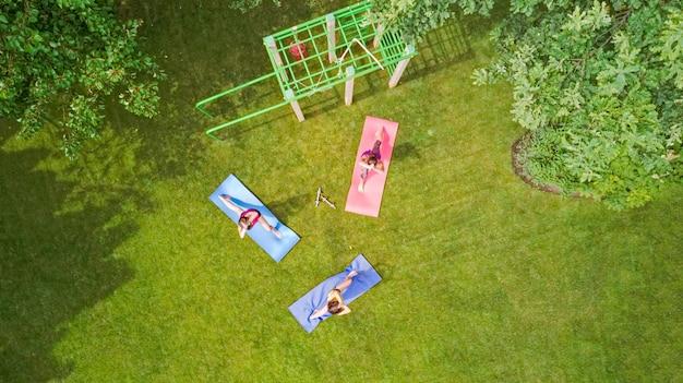 Familienfitness und sport im freien, gruppe von aktiven mädchen, die training im park, luftansicht von oben tun