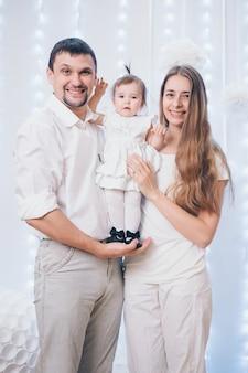 Familienfoto auf einem weißen hintergrund, eltern verbringen zeit mit ihren kindern. mama und papa umarmen das baby.