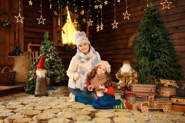 Familienfoto der mutter und der tochter, die auf den boden mit nettem kaninchen legen. weihnachtsdekoration