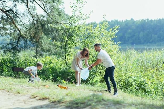 Familienfreiwilliger reinigt müll in der natur. vater und mutter, eltern, kinder, freiwillige der sohnfamilie an einem sonnigen tag, die die müllflaschen im debriwald aufräumen, die in plastiktüten falten