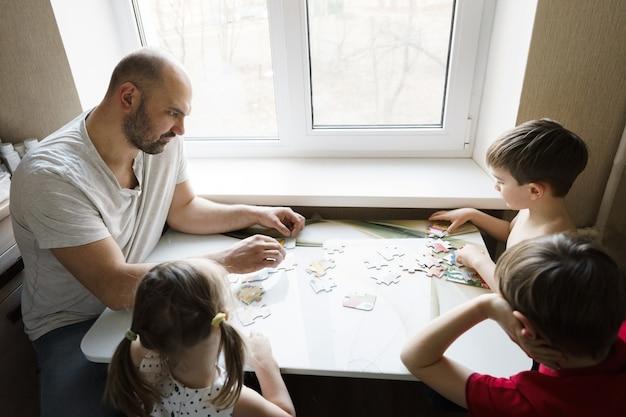 Familienfreizeit: vater, söhne und tochter spielen zusammen brettspiele