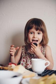 Familienfrühstück. mädchen mit eltern sitzen an einem tisch und essen croissants, kekse, trinken tee.
