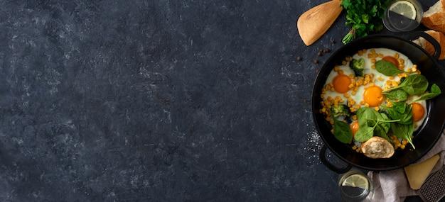 Familienfrühstückstisch mit draufsicht des spiegeleispinats und -maises über dunklen steinhintergrund mit copyspace