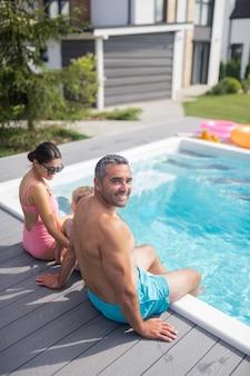 Familiengefühl entspannt. blick von oben auf die strahlende familie, die sich beim chillen in der nähe des pools entspannt fühlt