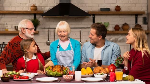 Familiengenerationen, die am erntedankabendtisch sitzen