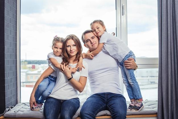 Familienglück mama, papa und zwei mädchen zwillingsschwestern zu hause im hintergrund des fensters.
