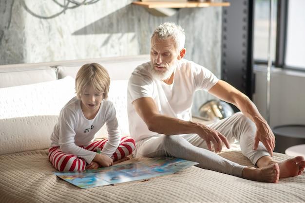 Familienheim. betroffener grauhaariger erwachsener mann und kind mit buch nebeneinander auf dem bett sitzend