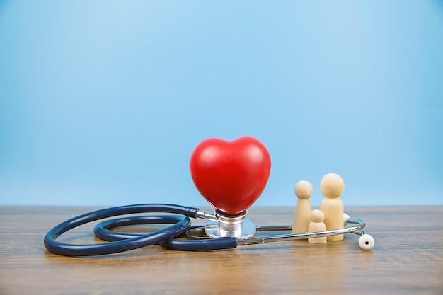Familienholzpuppe und rotes herz mit stethoskop.