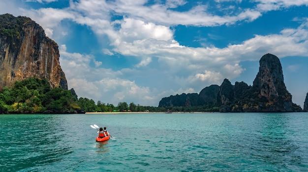 Familienkajakfahren im meer, mutter und tochter, die im kajak auf tropischer seekanutour nahe inseln paddeln, spaß haben, aktiven urlaub mit kindern in thailand, krabi