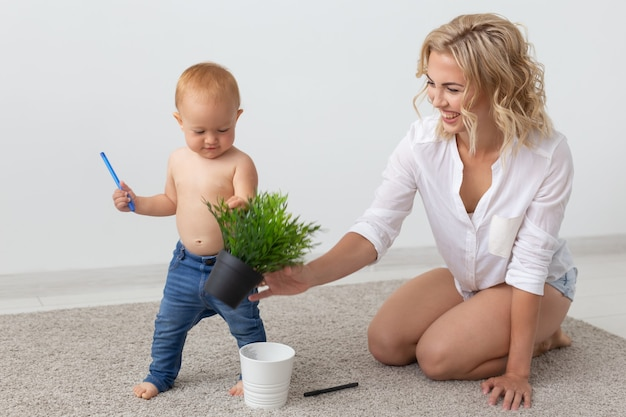 Familienkind- und elternschaftskonzept glücklich lächelnde junge mutter, die mit kleinem baby zu hause spielt