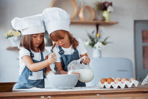Familienkinder in weißer kochuniform, die essen in der küche zubereiten.