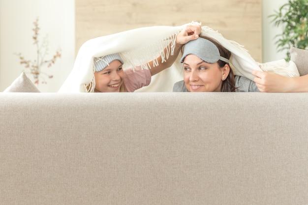 Familienkonzept der mutter und der tochter happ, tragende schlafmaske und spaß auf sofa im wohnzimmer