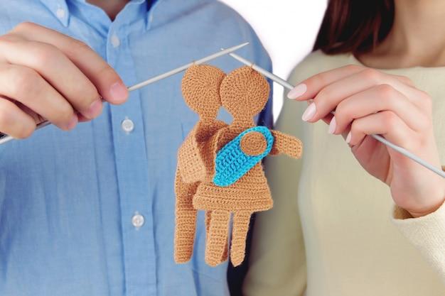 Familienkonzept. frau und mann, die gestricktes schattenbild der jungen familie mit neugeborenem baby durch gestrickte nadeln halten