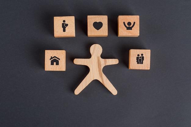 Familienkonzept mit ikonen auf holzwürfeln, menschliche figur auf dunkelgrauer tischflachlage.
