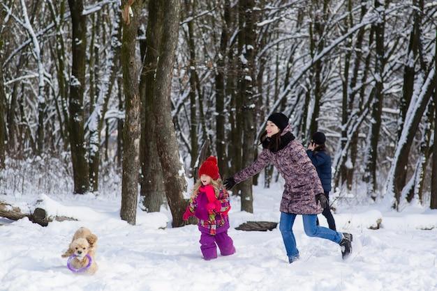 Familienlauf im schnee nach ihrem hund mit lila spielzeug