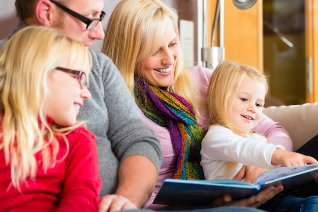 Familienlesegeschichte im buch auf sofa im haus