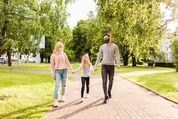 Familienmitglieder, die im park gehen, tragen stoffgesichtsmasken.