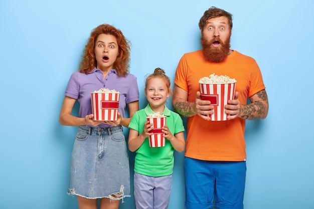 Familienmitglieder genießen es, mit popcorn fernzusehen