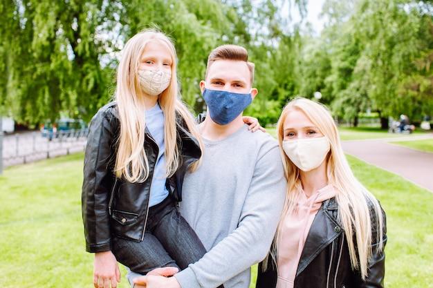Familienmitglieder umarmen sich und lächeln in der kamera mit stoffmasken.