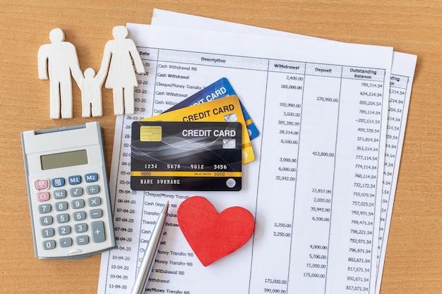 Familienmodell und taschenrechner auf kontoauszug und kreditkarte auf einem holztisch.