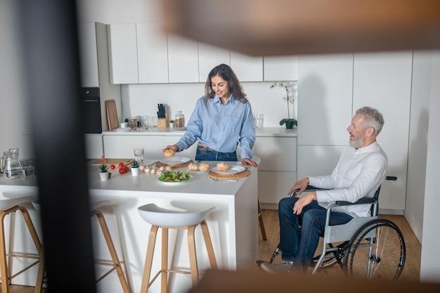 Familienmorgen. junge dunkelhaarige frau bereitet frühstück für ihren behinderten ehemann zu
