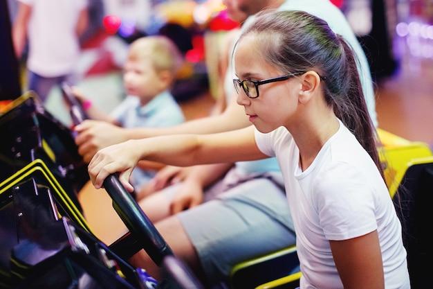 Familienmutter, vater, teenager-mädchen mit brille und kleiner junge, der auto-arcade in spielautomaten in einem vergnügungspark fährt. selektiver fokus.