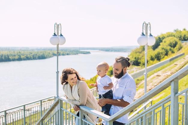 Familienmutter vater und baby glücklich mit einem lächeln zusammen im park, der entlang der promenade im sommerporträt geht