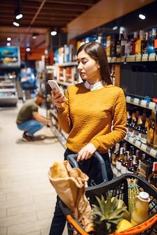 Familienpaar, das alkoholprodukte im lebensmittelgeschäft wählt