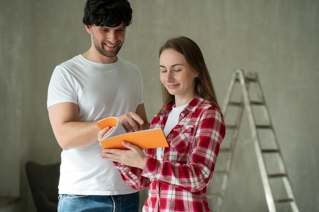 Familienpaar, das eine renovierung eines hauses mit farbpalette bespricht