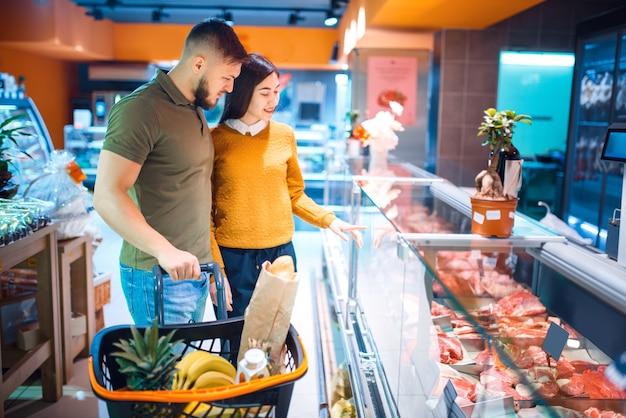 Familienpaar, das frisches gekühltes fleisch im lebensmittelgeschäft wählt