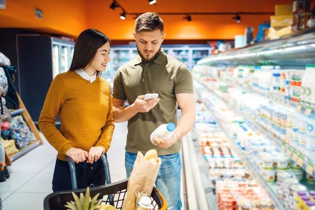 Familienpaar, das milch im lebensmittelgeschäft wählt, abteilung für milchprodukte